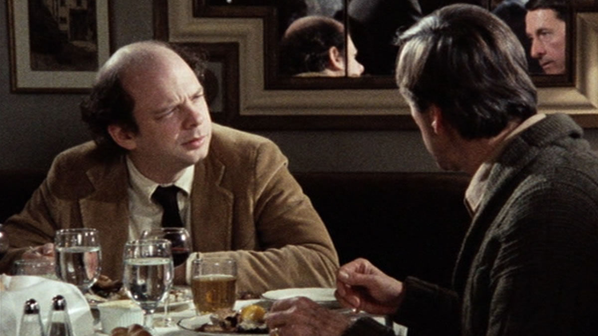 Wallace Shawn and Andre Gregory in ‎My Dinner with Andre (1981). Wallace (left), a white man with a bald patch atop his head and wearing a camel-coloured velvet suit and black tie, is sitting at an elaborately-set dinner table. Opposite him is Andre, whose dark hair can only be seen as he faces away from the camera, in conversation with Wallace. He wears a grey suit jacket.