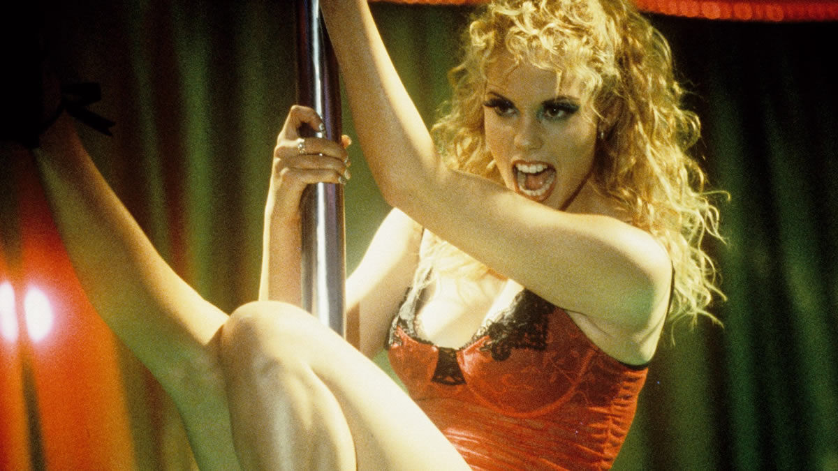 ‎Showgirls (1995). Nomi, a blonde white woman with her hair curled, hangs from a pole during a performance, one of her legs stretched into the air. She is wearing a red lacy outfit with a black trim, and heavy makeup.