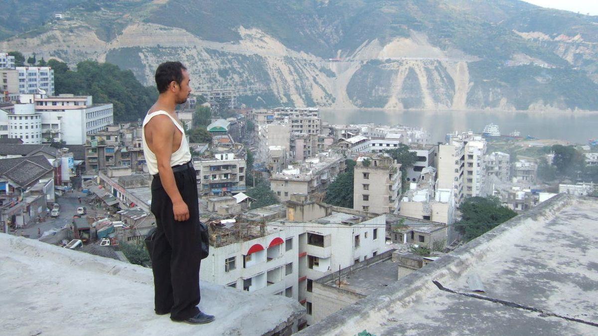 Homem olhando para prédios devastados